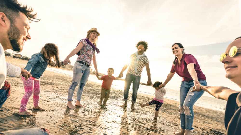 Family holding hands in a circle on a beach